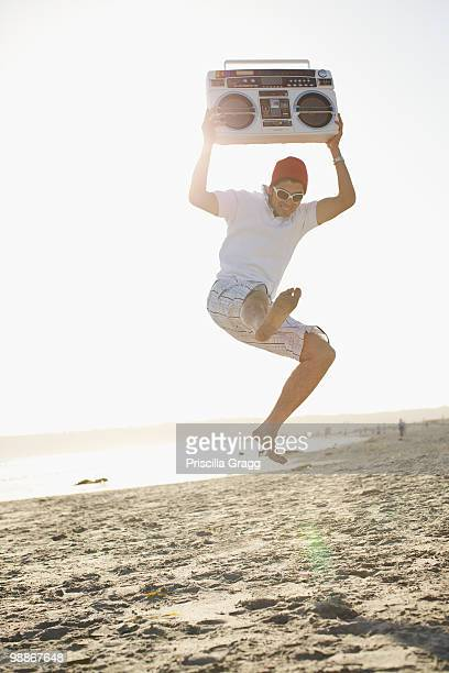 Hispanic man holding boom box and jumping