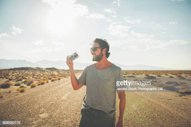 Hispanic man holding camera on remote road
