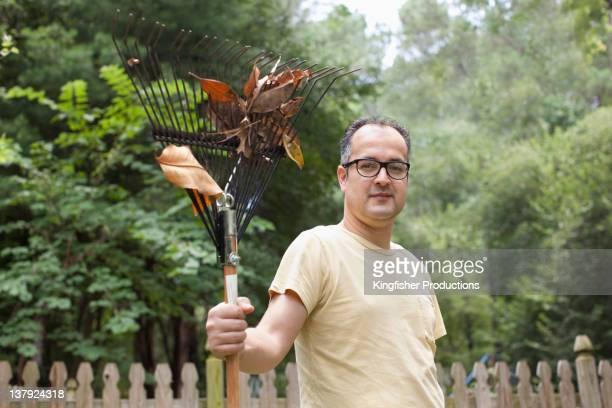 Hispanic man holding rake in yard