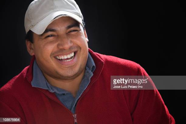 Hispanic man in baseball cap laughing
