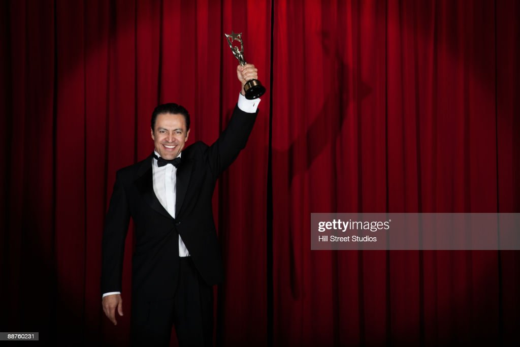 Hispanic man in tuxedo holding trophy onstage : Stock Photo