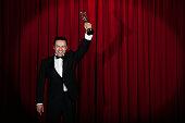 Hispanic man in tuxedo holding trophy onstage