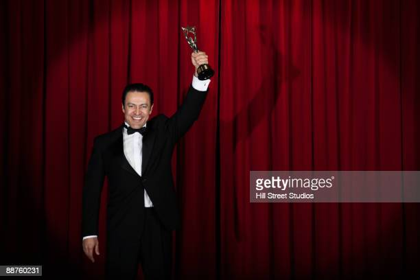 Hispanic man in tuxedo holding trophy onstage