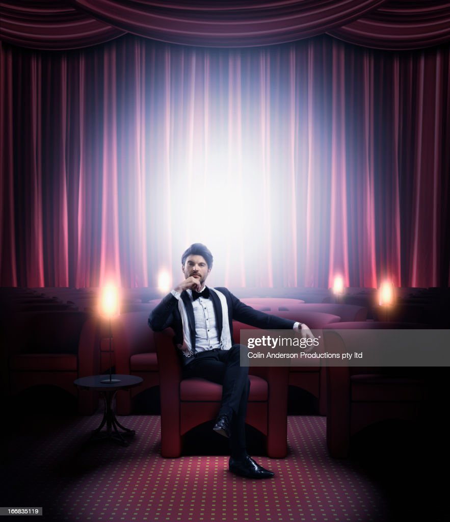 Hispanic man in tuxedo sitting in empty lounge