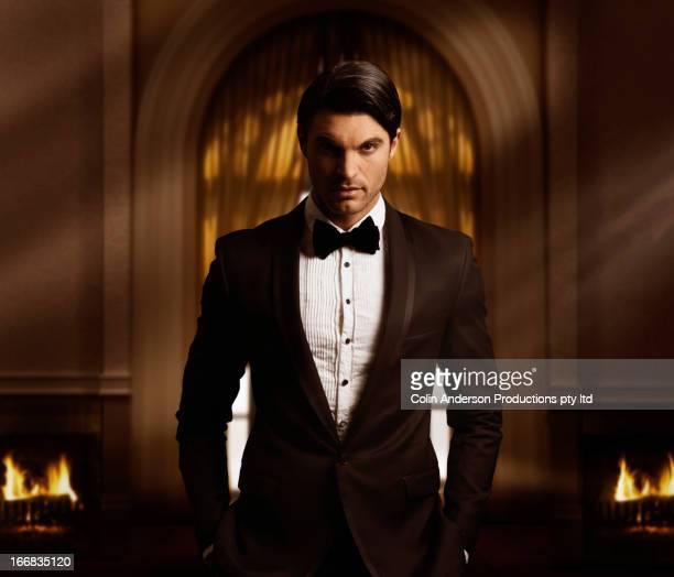 Hispanic man in tuxedo standing in living room