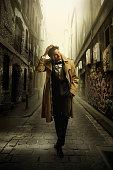 Hispanic man in tuxedo walking in city alleyway