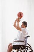Hispanic man in wheelchair shooting basketball
