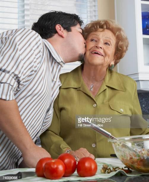 Hispanic man kissing mother on cheek
