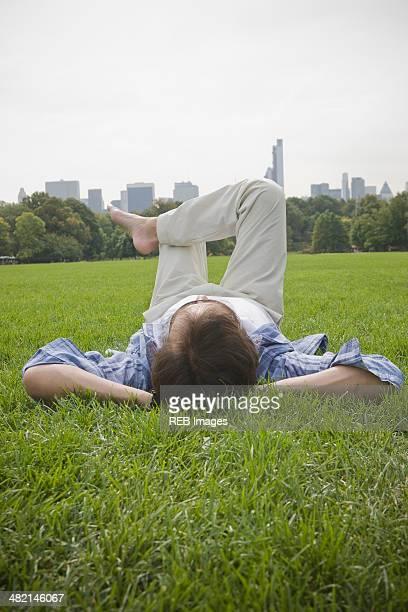Hispanic man laying in grass at park