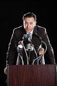 Hispanic man leaning on podium with microphones