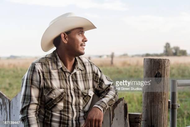 Hispanic man leaning on wooden fence