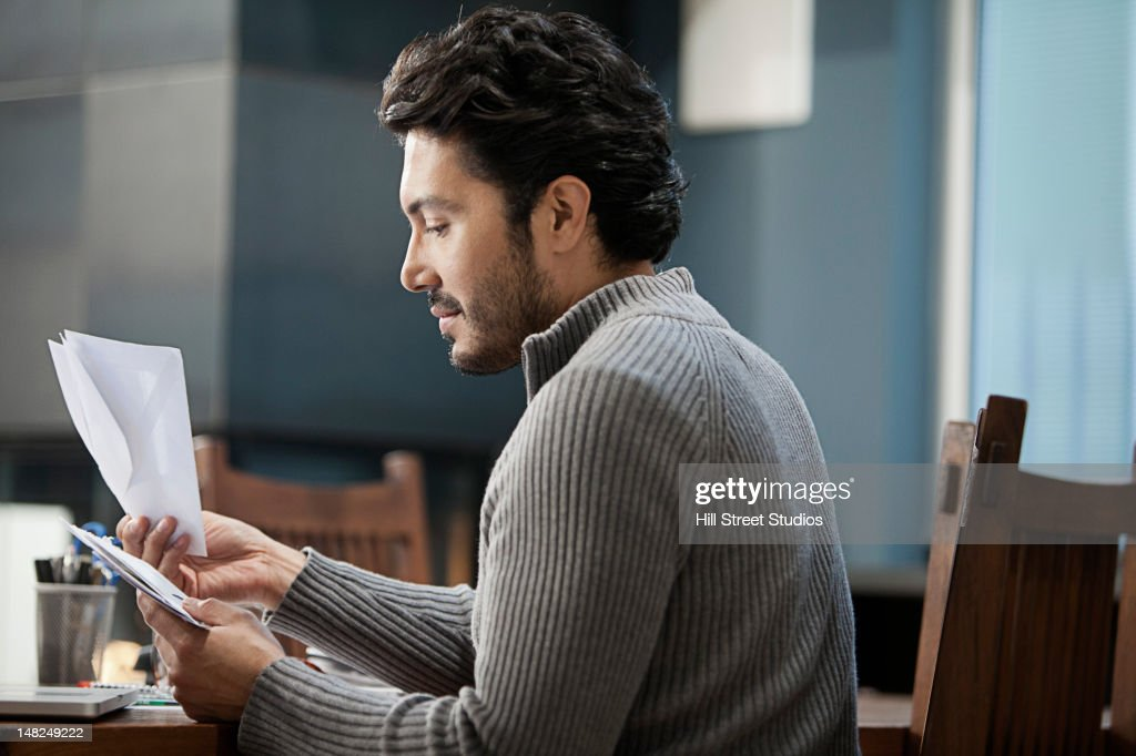 Hispanic man looking at bills : Stock Photo