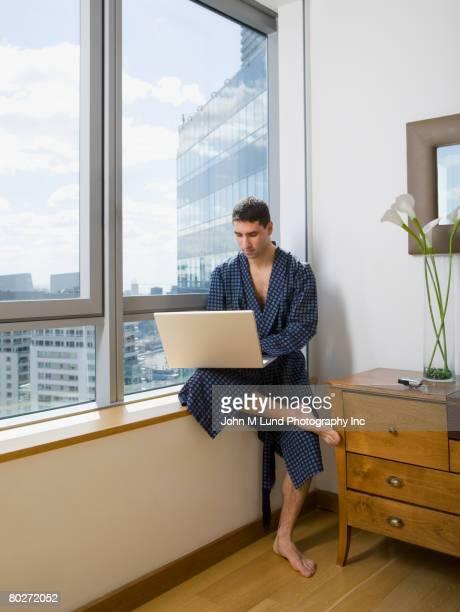 Hispanic man looking at laptop