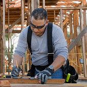 Hispanic man measuring wood plank