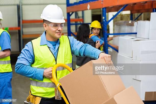 Déplacement de boîtes d'homme hispanique avec chariot de occupé entrepôt