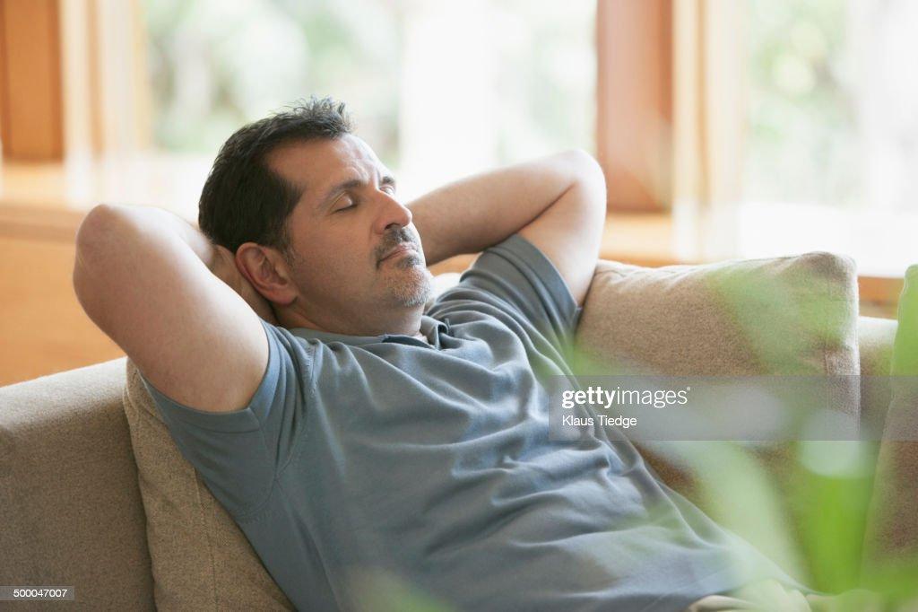 Hispanic man napping on sofa