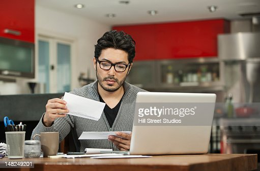 Hispanic man paying bills on computer : Stock Photo