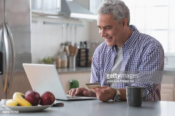Hispanic man paying bills online in kitchen