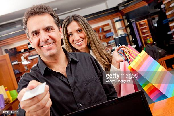 Hispanic man paying for shopping with credit card