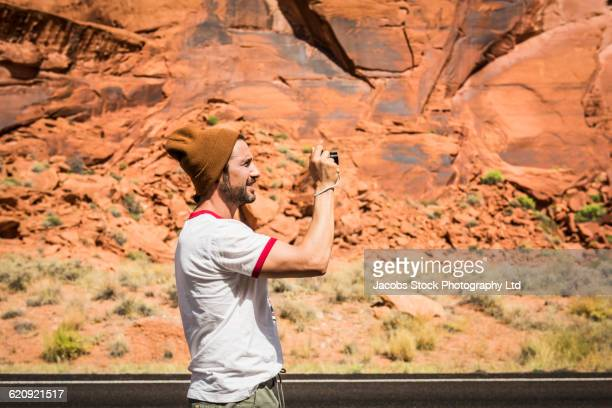 Hispanic man photographing rock formation