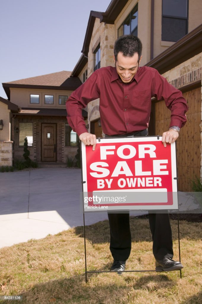 Hispanic man placing for sale sign in yard : Stock Photo