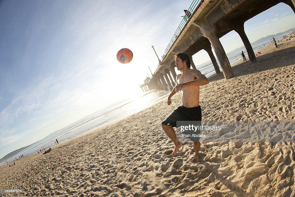 Hispanic man playing with soccer ball on beach : Stock Photo