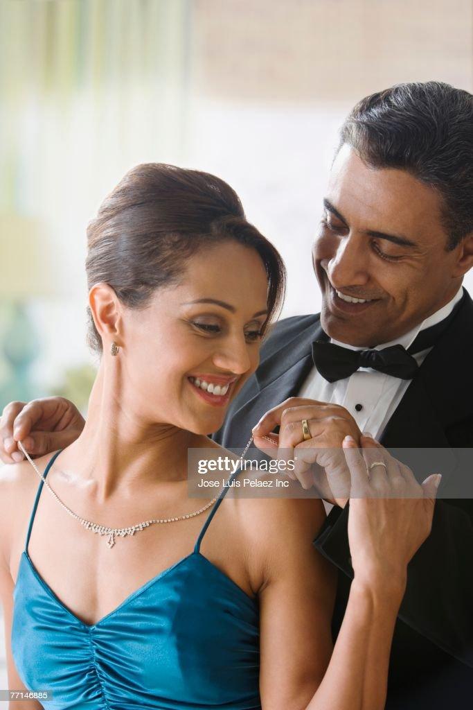 Hispanic man putting diamond necklace on wife