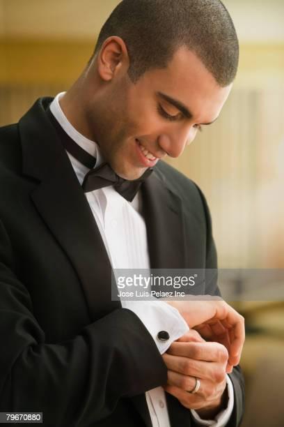 Hispanic man putting on cufflinks