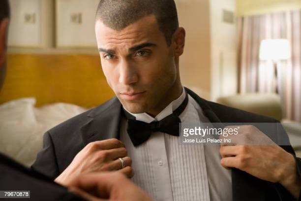 Hispanic man putting on tuxedo jacket
