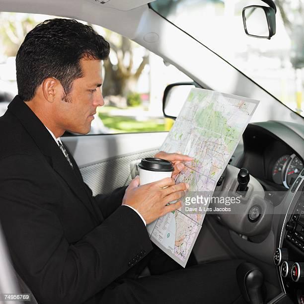 Hispanic man reading map in car