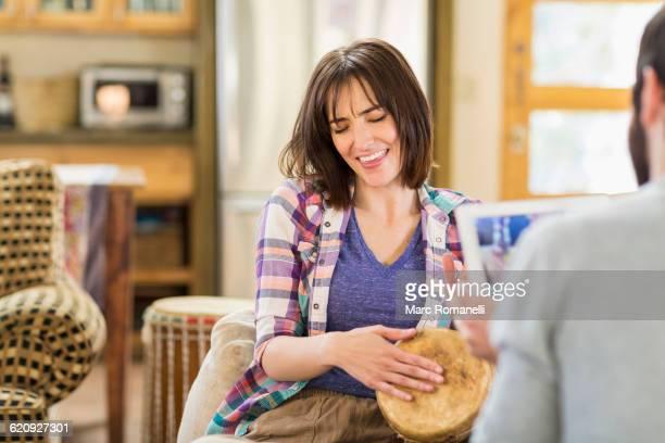 Hispanic man recording girlfriend playing drums