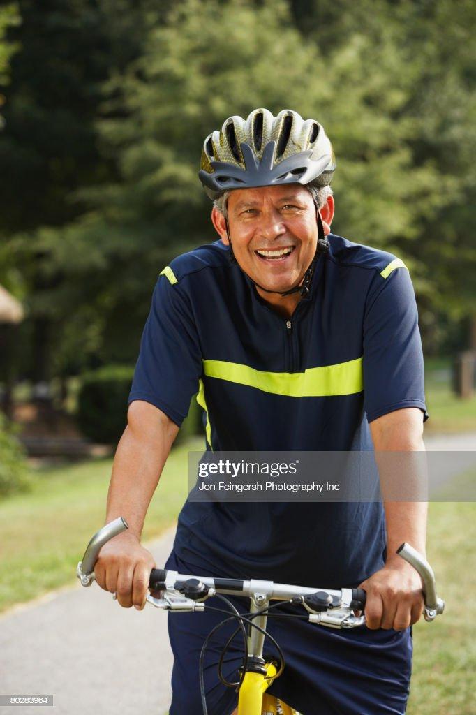 Hispanic man riding bicycle : Stock Photo