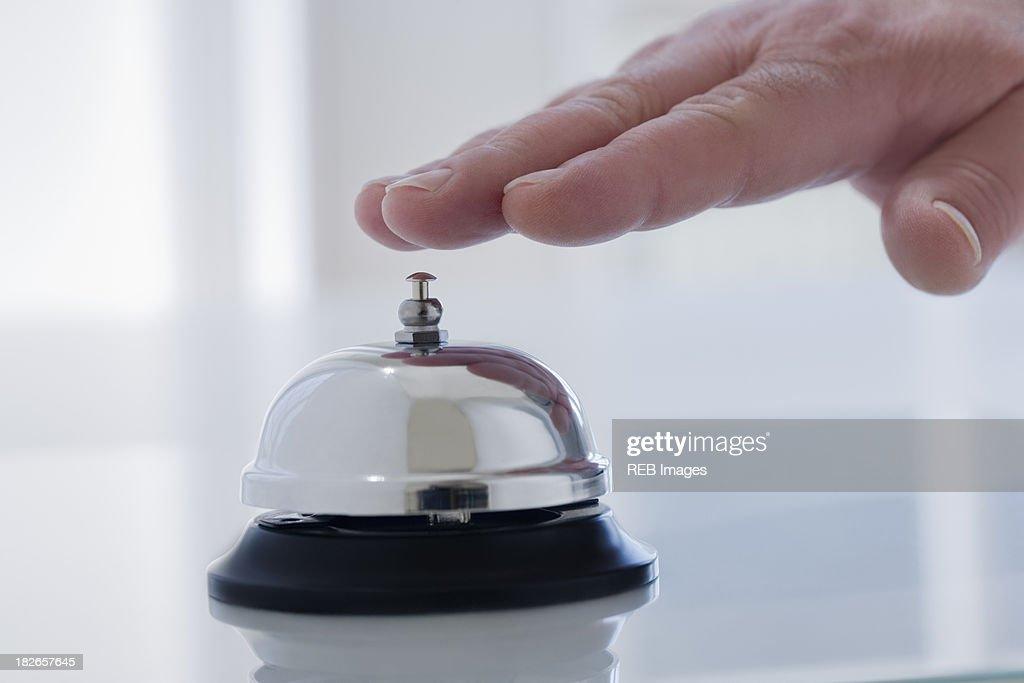 Hispanic man ringing service bell on desk