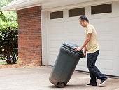 Hispanic man rolling garbage can