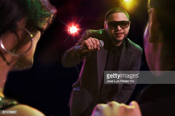 Hispanic man singing in nightclub