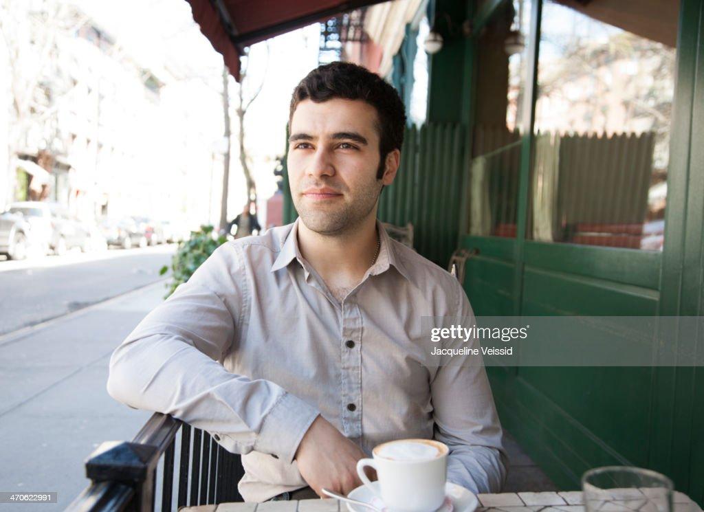 Hispanic man sitting at sidewalk cafe