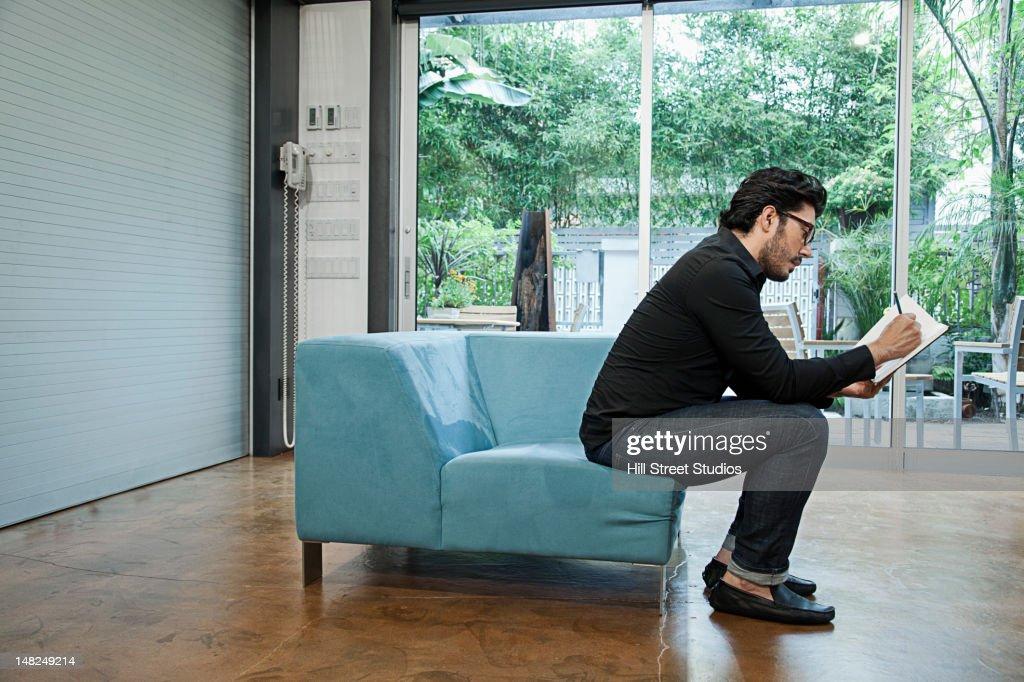 Hispanic man sitting in chair sketching : Stock Photo