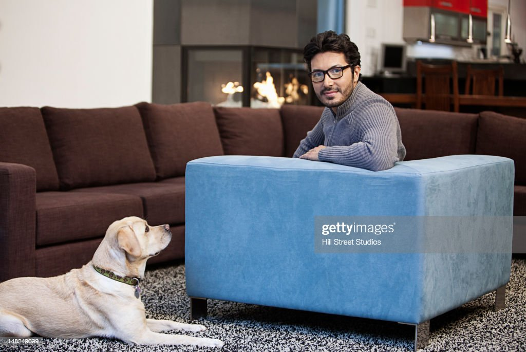 Hispanic man sitting in living room with dog : Stock Photo