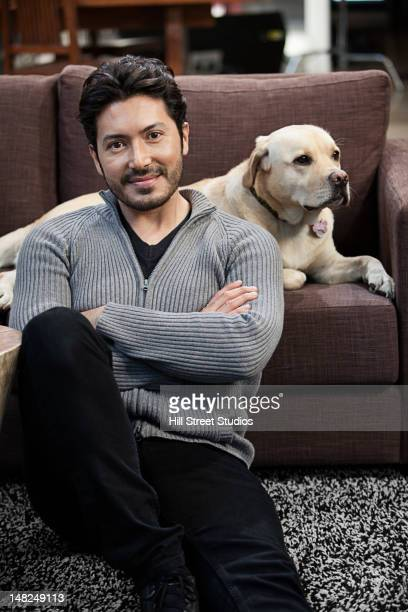 Hispanic man sitting in living room with dog