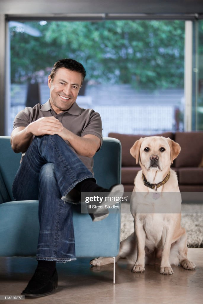 Hispanic man sitting in living room with dog : Stock Photo