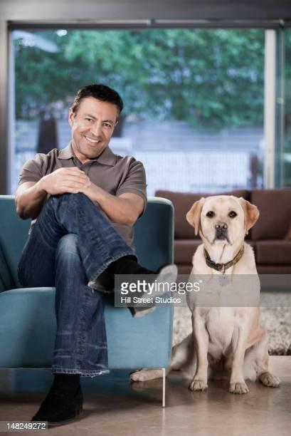 Hispanic homme assis dans la salle de séjour avec un chien