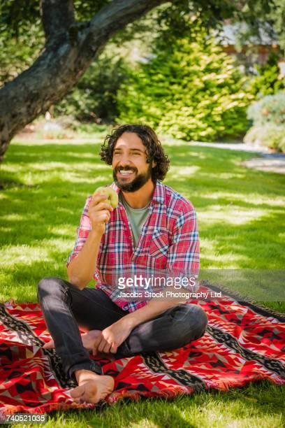 Hispanic man sitting on blanket in grass eating fresh apple