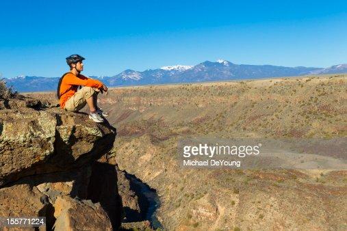 Hispanic man sitting on canyon cliff