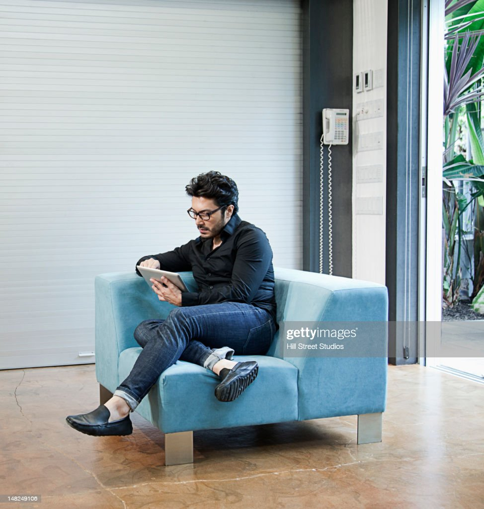 Hispanic man sitting on chair using digital tablet