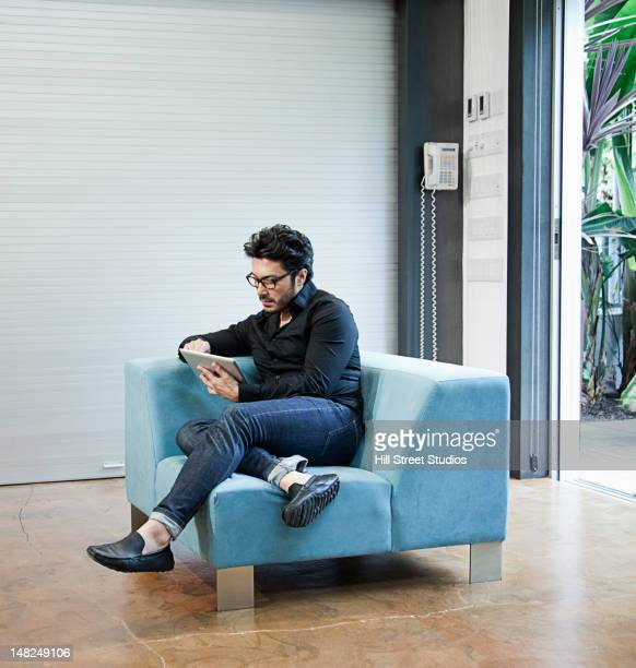 Hispanic man sitting on chair using digital tablet