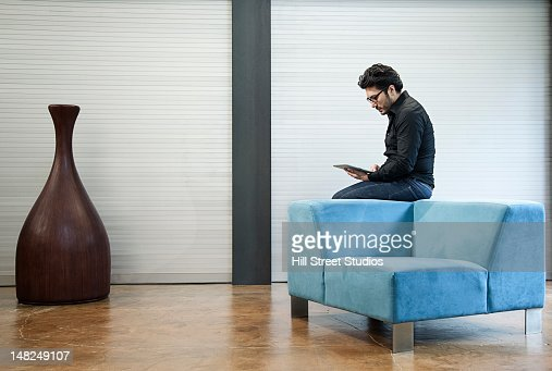 Hispanic man sitting on chair using digital tablet : ストックフォト