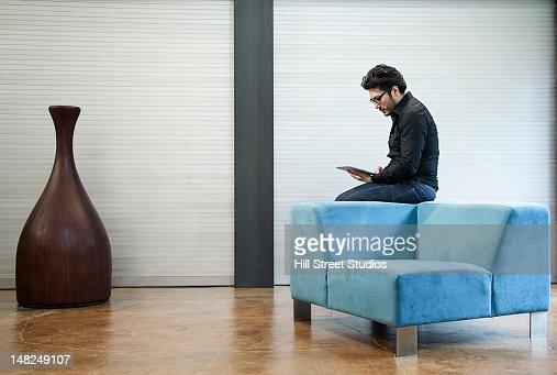 Hispanic man sitting on chair using digital tablet : Stock Photo