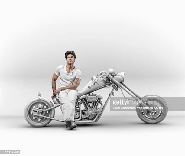 Hispanic man sitting on motorcycle