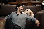 Hispanic man sitting with dog in living room