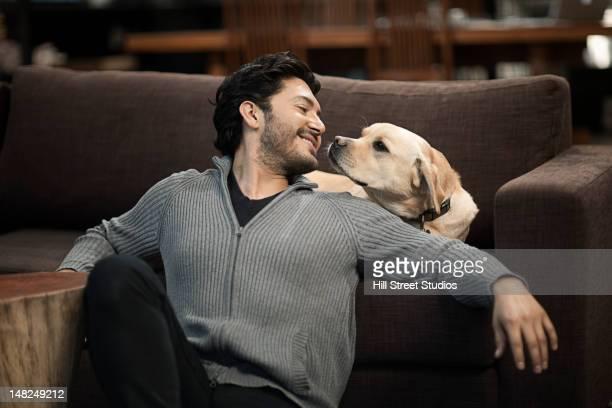 Hispanic homme assis avec chien dans la salle de séjour